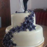 Svatební dort s fialovými květy a figurkami